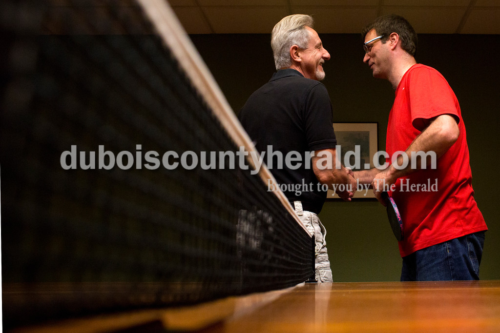 Tegan Johnston/The Herald<br /> Gary Metzgar of Huntingburg, left, congratulated Mark Buse of Jasper after a match during a ping pong tournament Saturday at Dan Fritch's home in Jasper. On Saturday afternoons throughout the winter months, a group of 8-18 men will gather at each other's homes, ante up $1 and randomly pair off to compete in matches of doubles.