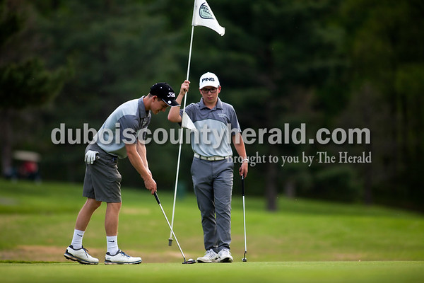 Tegan Johnston / The Herald Jasper's Jack Bies, lifted a flag out of the hole as his teammate Carson Pierce putted during a match against Southridge on Wednesday at Buffalo Trace Golf Course in Jasper. Jasper beat Southridge 157-180.