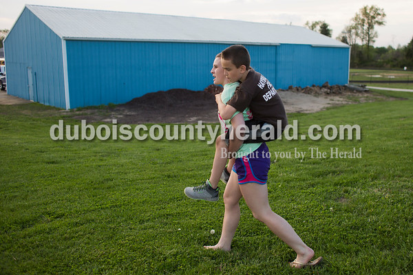 Northeast Dubois freshman Makena Everman gave her nine-year-old brother CJ a piggy back ride after Thursday's baseball game in Dubois. Northeast Dubois defeated Wood Memorial 11-1 in six innings. Sarah Ann Jump/The Herald