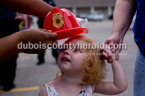 Tegan Johnston / The Herald Lauren Pitrowski of Jasper, 2, held the hand of her grandmother, Jeannine Martin of Jasper, as a Jasper firefighter tried to place a hat on her head during Fifth Street School's Community Health Fair on Thursday in Jasper. Thirty-six vendors set up at the school to promote healthy living with nutritious snacks and a variety of activities for families to enjoy.