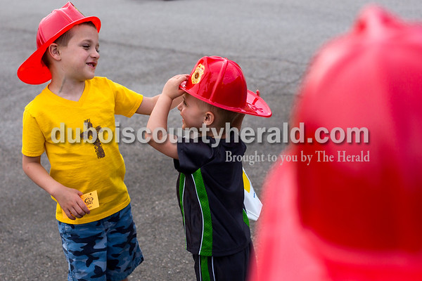 Tegan Johnston / The Herald Grant Gehlhausen of Ireland, 8, watched his younger brother, Cash, 4, left, help Max, 2, adjust the hat he received from the Jasper Fire Department during Fifth Street School's Community Health Fair on Thursday in Jasper. Thirty-six vendors set up at the school to promote healthy living with nutritious snacks and a variety of activities for families to enjoy.