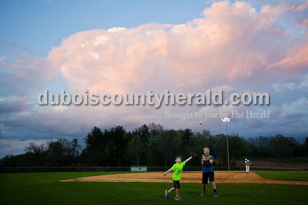Koby Greulich, 5, left, son of assistant coach Kyle Greulich, and Bryson Frick, 10, both of Ferdinand, played catch on the field after Tuesday night's game against Castle in Ferdinand. A rain cloud passed over the field during the end of the game, leaving a hint of moisture and a small rainbow as it passed. The Rangers lost 10-3.   Alisha Jucevic/The Herald