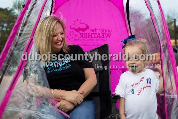 Brynley Woolems of Dubois, 2, showed off her popsicle-tinted blue tongue as she visited Tammy Ziegler of Dubois in her personal weather tent during Thursday's baseball game in Dubois. Northeast Dubois defeated Wood Memorial 11-1 in six innings. Sarah Ann Jump/The Herald