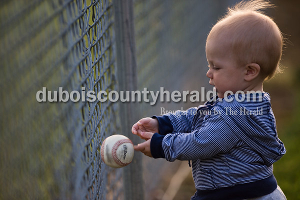 Kenton Heeke of Dubois, 1, played with his uncle Case Eisenhut's home run ball during Thursday's baseball game in Dubois. Northeast Dubois defeated Wood Memorial 11-1 in six innings. Sarah Ann Jump/The Herald