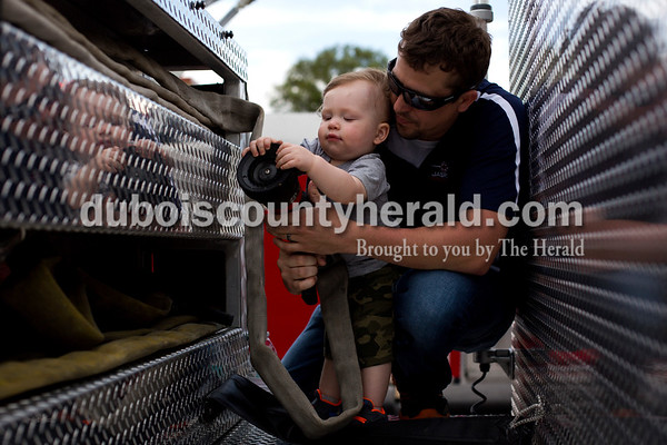 Tegan Johnston / The Herald Jasper firefighter Brad Hochgesang held onto his 15-month-old son Carson as he showed him a hose on the fire truck during Fifth Street School's Community Health Fair on Thursday in Jasper. Thirty-six vendors set up at the school to promote healthy living with nutritious snacks and a variety of activities for families to enjoy.