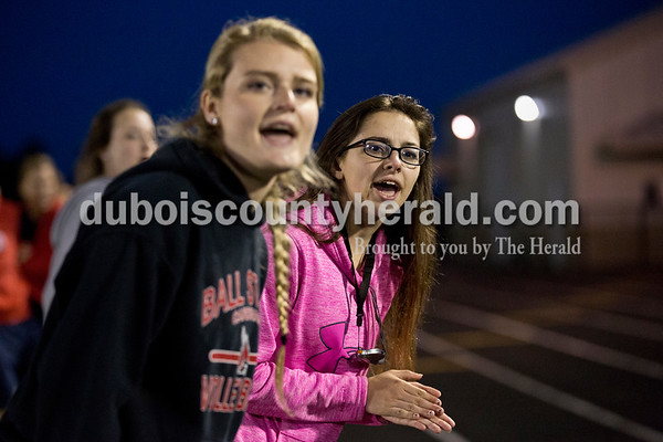 Heritage Hills' Brooke Dougan, left, and Cassidy Stiles cheered on their teammates competing in the 1600-meter relay during Thursday's Southridge Invitational in Huntingburg. Sarah Ann Jump/The Herald