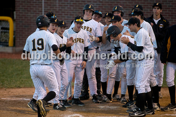 The Wildcats crowded around home plate to congratulate Evan Aders after he hit a home run during Thursday night's game at Ruxer Field in Jasper. The Wildcats won 7-0.  Alisha Jucevic/The Herald