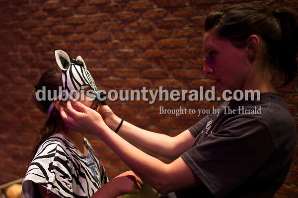 "Sarah Ann Jump/The Herald Lincoln Trail Elementary School fourth-grader Audrey Norrick tried on her zebra costume with the help of her mother Bethany Norrick, a back stage volunteer, during Tuesday's ""Lion King Jr."" play rehearsal at Heritage Hills High School in Lincoln City."