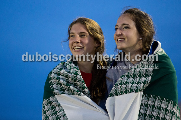 Heritage Hills' Marlee Vinson, left, and Karlie Tischendorf shared a blanket as they watched their teammates compete during Thursday's Southridge Invitational in Huntingburg. Sarah Ann Jump/The Herald