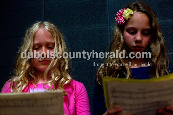 Tegan Johnston / The Herald Celestine Elementary School fourth-graders Hannah Bachman, left, and Bella Beckman reviewed their piano music before performing during Celestine Elementary School's spring music program on Thursday at Dubois Middle School. The third and fourth grade classes performed a variety of musical arrangements, from singing to playing on the ukulele, piano, violin or guitar.