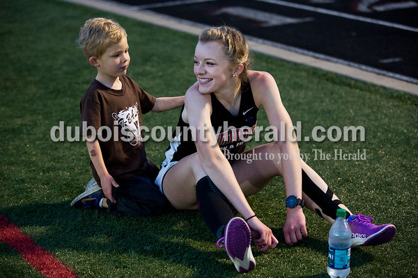 Landon Tretter, 4, rubbed the back of his sister, Southridge freshman Brooklyn Tretter, after she competed in the 800-meter run during Thursday's Southridge Invitational in Huntingburg. Sarah Ann Jump/The Herald