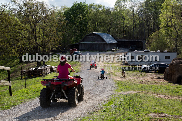 Craig Englert, center, rode ATVs with his sister Katelyn Englert, 16, left, as their nephew, Wren Englert, 3, rode a dirt bike at their Birdseye home on April 18.