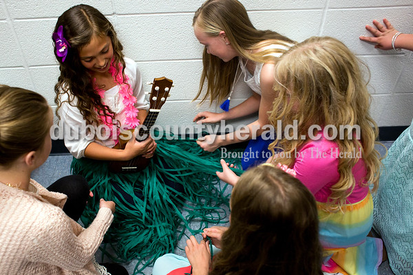 Tegan Johnston / The Herald Celestine Elementary School fourth-grader Makenzie Buchta waited to perform in a hall backstage while her classmates braided together her hula skirt during Celestine Elementary School's spring music program on Thursday at Dubois Middle School. The third and fourth grade classes performed a variety of musical arrangements, from singing to playing on the ukulele, piano, violin or guitar.