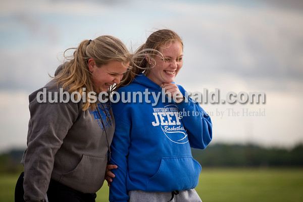 Northeast Dubois' Emily Kieffner, left, and Paige Jacob laughed together after one of Kieffner's discus throws during Thursday's Southridge Invitational in Huntingburg. Sarah Ann Jump/The Herald