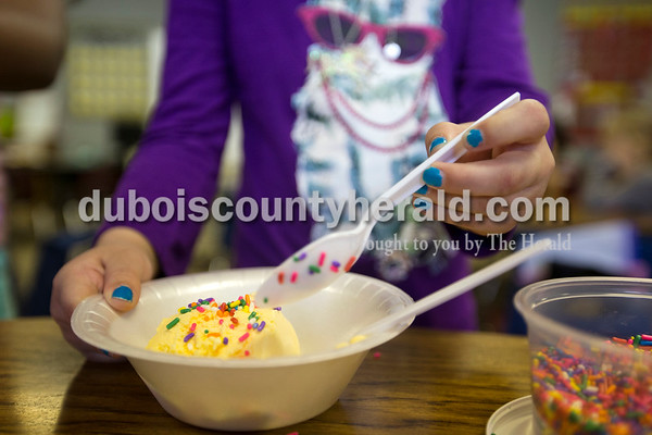 Fifth Street School kindergartner Morgan Hoffman splashed sprinkles on her ice cream during one classroom's sundae party for Fun Friday on Friday afternoon in Jasper.    Alisha Jucevic/The Herald