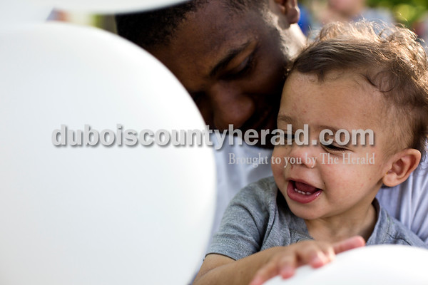 Tegan Johnston / The Herald Byron Moton of Jasper, held his 17-month-old son, Bryson, as he played with balloons during the Kids' Fest on Wednesday at Jaycee Park in Jasper. The Dubois County Department of Child Services partnered with other local child advocacy agencies to raise awareness for the prevention of child abuse. Families enjoyed food, games and other activities while learning about child abuse prevention services.