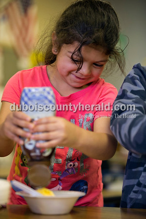 Fifth Street School kindergartener Irma Solis Graciano swirled chocolate sauce on a scoop of ice cream during one classroom's sundae party for Fun Friday on Friday afternoon in Jasper.   Alisha Jucevic/The Herald