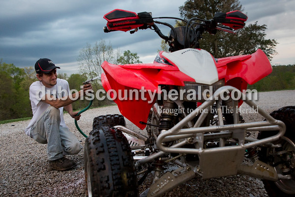 Craig Englert washed his ATV after riding at his Birdseye home on April 18.