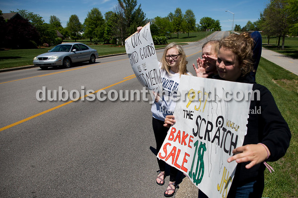 Sarah Ann Jump/The Herald Jasper High School juniors Averia Himself, left, Hannah Welp and Ashley Haskins attracted customers with signs during a bake sale at the school on Monday afternoon.