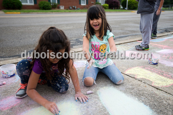 Fifth Street School first-graders Samantha Branham, left, and Hayzel Posada Garcia drew with calk outside the school during their Fun Friday period on Friday afternoon in Jasper.   Alisha Jucevic/The Herald