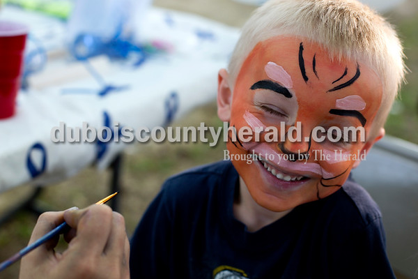 Tegan Johnston / The Herald Will Werner of Jasper, 4, pulled away as the paint brush Corina Mack, with Jasper Community Arts Commission, was using tickled his cheek during the Kids' Fest on Wednesday at Jaycee Park in Jasper. The Dubois County Department of Child Services partnered with other local child advocacy agencies to raise awareness for the prevention of child abuse. Families enjoyed food, games and other activities while learning about child abuse prevention services.