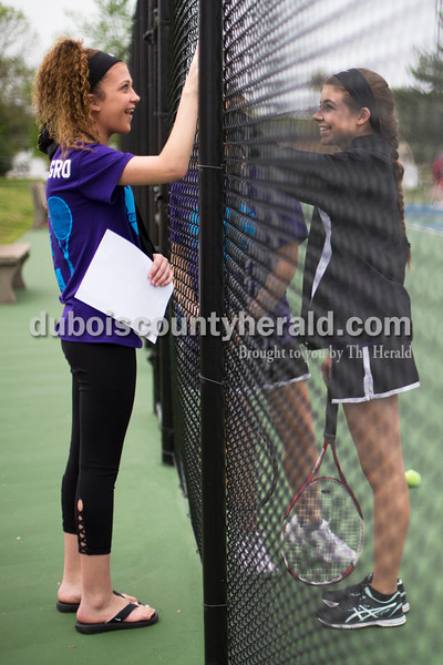 Sarah Ann Jump/The Herald<br /> Southridge High School sophomore Lexi Mattingly of Holland, 16, talked with tennis teammate Emma Kinker through the court fence before a tennis match at the school in Huntingburg on Monday.