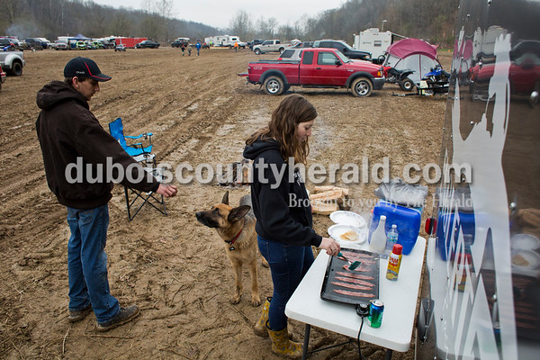 Craig Englert of Birdseye distracted their dog Shep as his girlfriend Jade Hoffman of Celestine made bacon and pancakes for breakfast before the ATV race in Gosport on April 1. The couple converts the trailer that hauls Craig's ATV into a bed for camping at races across the state.