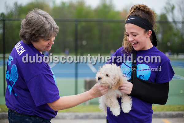 "Sarah Ann Jump/The Herald Southridge High School sophomore Lexi Mattingly of Holland, 16, right, introduced her 15-week-old puppy Presley to tennis head coach Rhonda Diekhoff before a tennis match at the school in Huntingburg on Monday. Lexi convinced her parents to get her a puppy after she received the news that she would need further surgery for her heart condition. The team wore matching shirts that read ""Luv for Lexi""."