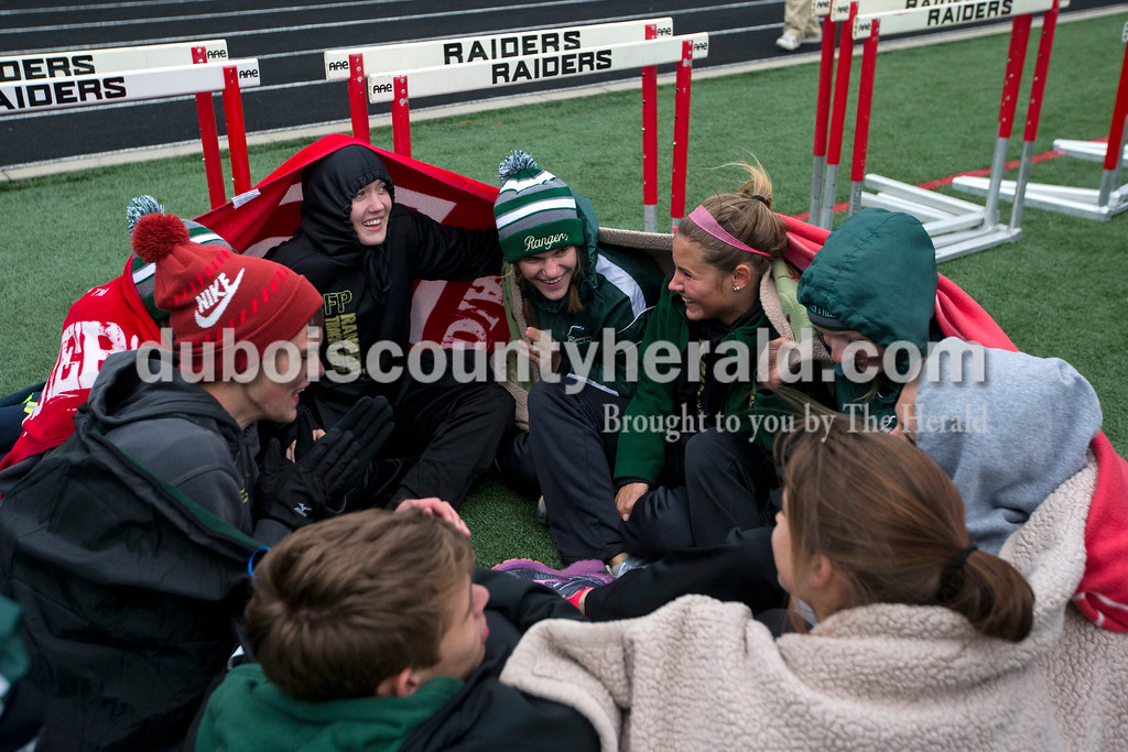 Members of the Forest Park track team huddled together to stay warm as they waited for their next event during Monday night's track meet at Southridge High School in Huntingburg.   <br /> Alisha Jucevic/The Herald