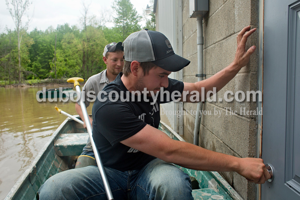 Max Hasenour of Celestine was unable to open the door to Tri-State Live Haul in the Witz Bottoms in Jasper on Sunday as he and Casey Kern  of Schnellville inspected the floodwaters around he building.