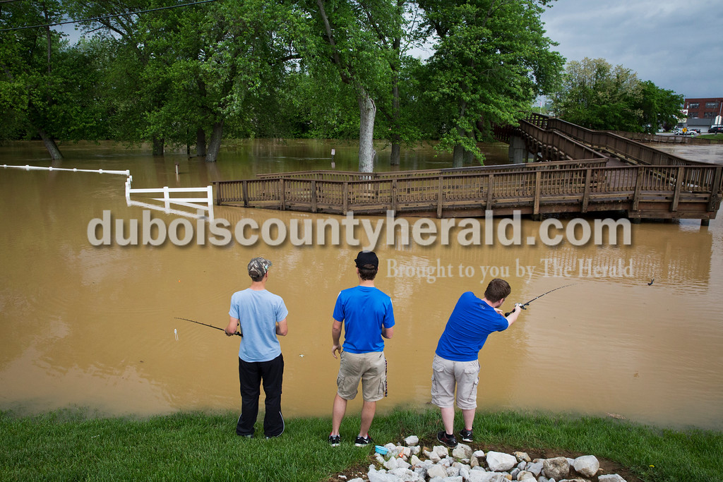 """Sarah Ann Jump/The Herald<br /> Cody Schnell, 17, left, Andrew Jespersen, 17, and Skyler Kubler, 16, all of Jasper, fished in the floodwaters near the Riverwalk in Jasper on Sunday afternoon. """"I'm hoping to catch some bass that may swim up where it's shallower,"""" said Cody Schnell."""