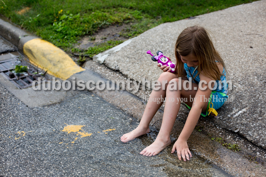 Justice Matthews of Huntingburg, 8, sat outside and played in the storm water Saturday after the home she shares with her mother, Theresa McKnight, experienced flooding.