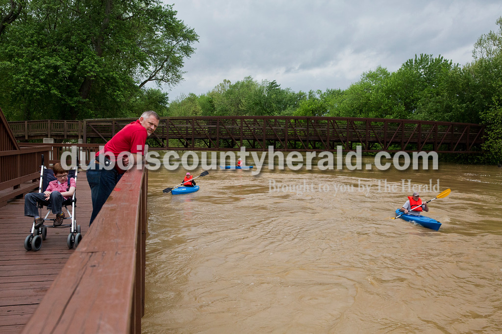 Sarah Ann Jump/The Herald<br /> Abe Wanninger of Jasper, 9, left, and his father Jason visited the Jasper City Mill to view the Patoka River flooding as Marla Haas of Celestine, Terri Jacob of Ireland and her husband Kevin Jacob kayaked in Jasper on Sunday afternoon.