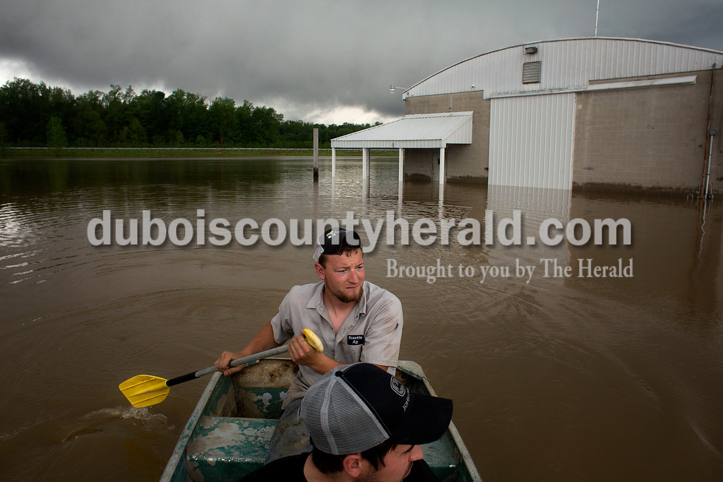 Casey Kern of Schnellville and Max Hasenour of Celestine paddled back to dry land after inspecting the floodwaters surrounding Tri-State Live Haul in the Witz Bottoms in Jasper on Sunday afternoon. Casey's father Jerry owns the business and said that the floodwaters spilled over the levy they had built up higher after the last time the businesses flooded in 2008. Dave Weatherwax/The Herald