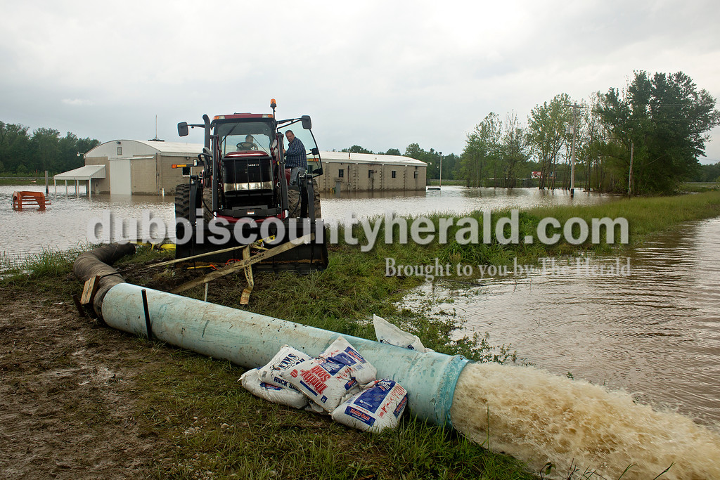 Brad Hochgesang of Jasper and Jerry Kern of Schnellville pumped water out from behind that levy that was designed to protect Jerry's business, Tri-State Live Haul, from floodwaters in the Witz Bottoms in Jasper on Sunday afternoon. Dave Weatherwax/The Herald