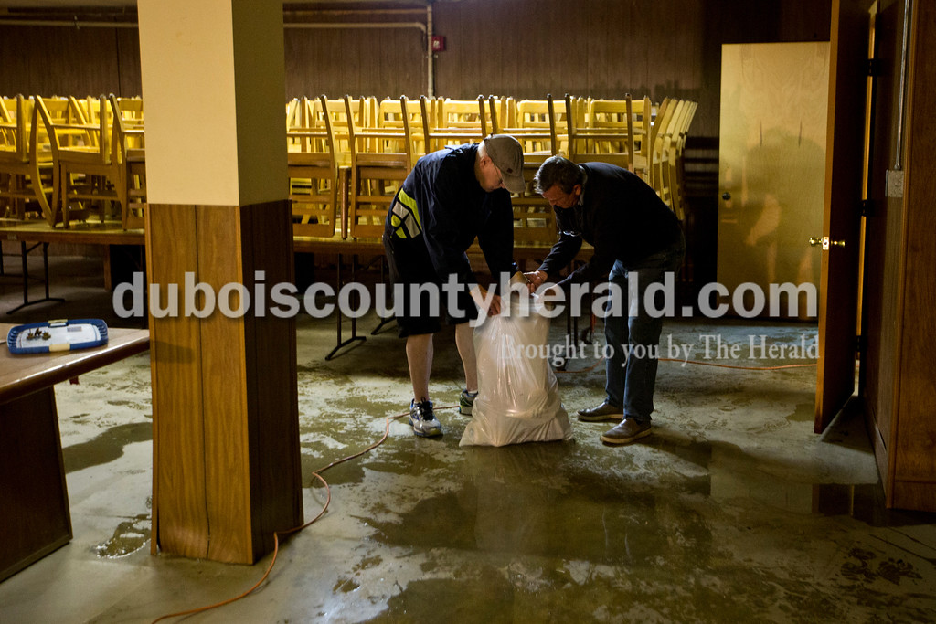 Don Dotterweich and Jim Potter of Huntingburg cleaned out the remaining water and damaged supplies at the Huntingburg V.F.W. Post #2366 on Monday afternoon.  <br /> Alisha Jucevic/The Herald