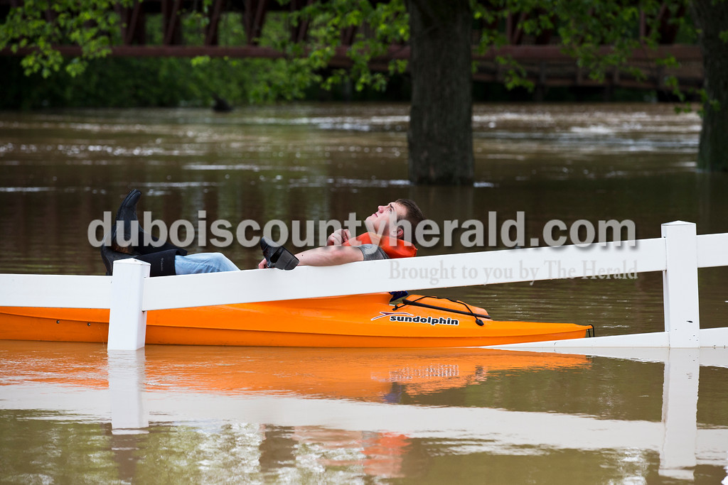 Sarah Ann Jump/The Herald<br /> Resting in his kayak along a submerged fence, Reid Haas of Celestine scanned the sky as storm clouds approached near the Riverwalk in Jasper on Sunday afternoon.
