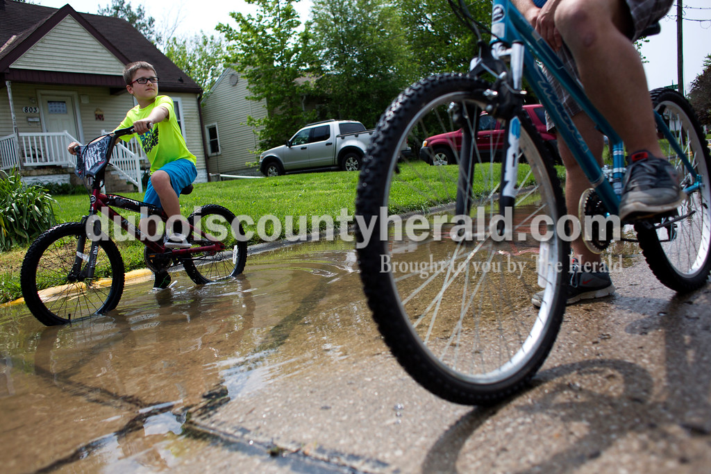 Michael Lau of Huntingburg, 10, biked over with his father, Todd, to check on their relatives Kristy Lawrence and her daughter, Kristyn, 16, after storms flooded many of the homes in the Huntingburg neighborhood Saturday.