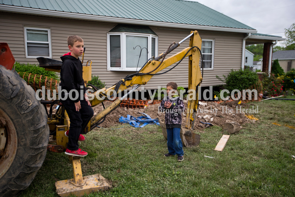 A long section of the foundation and basement wall caved in under Rene Katterhenry's home on East 1st Avenue and South Washington Street in Huntingburg during last weekend's storm. Rene's son Reese, 9, left, and Reese's cousin Aiden, 7, stood next to their grandfather's tractor as they visited the house with Rene on Monday afternoon. Rene and her sons are staying with family while they figure out what insurance will cover and how they can repair the home. <br /> <br /> Alisha Jucevic/The Herald