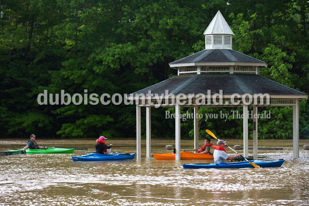 """Sarah Ann Jump/The Herald<br /> Danny Haas of Celestine, from left, his wife Marla, their son Reid and  Kevin Jacob of Ireland kayaked around the submerged Dave Buehler Plaza along the flooded Patoka River in Jasper on Sunday afternoon. """"This is the worse I've ever seen it,"""" said Jacob."""