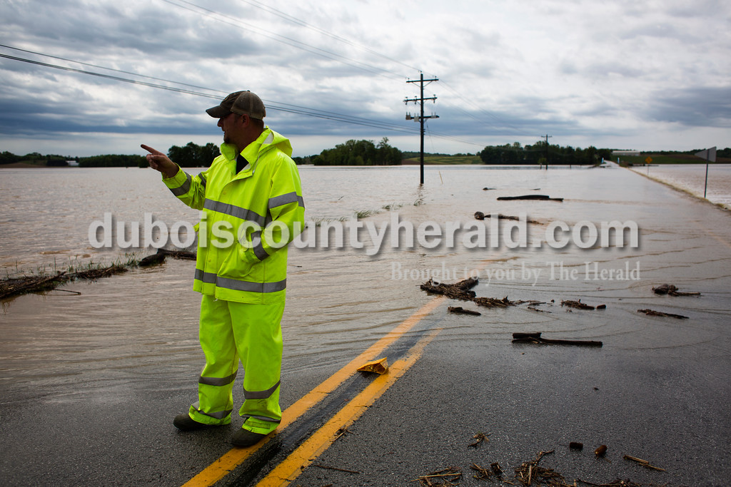 Jasper Volunteer Fireman Nick Nowakowski observed where water flooded Indiana State road 162 towards Ferdinand on Saturday. The fire department closed down the road and redirect traffic after rescuing  three stranded vehicles earlier that morning.