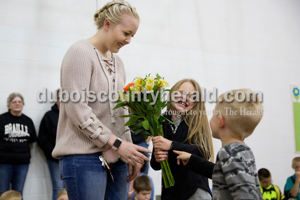 Sarah Ann Jump/The Herald<br /> Dubois Elementary School second-grader Kaylei Carie, who is blind, <br /> received flowers from her cousin Bethany Kempf of Haysville, left, as her 5-year-old cousin Hurley Luker of Dubois came up to congratulate her at the school in Dubois on Friday afternoon.