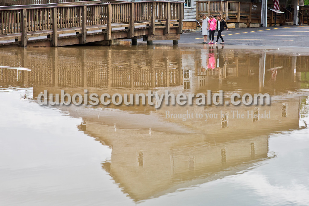 """Sarah Ann Jump/The Herald<br /> Ellie Cox, left, and twin sisters Natilee and Ashlee Wahl, all 12 and of Huntingburg, stood along the floodwaters near Jasper City Mill and the Riverwalk in Jasper on Sunday afternoon. """"It's horrible,"""" said Ellie. """"But fun,"""" added Ashlee."""
