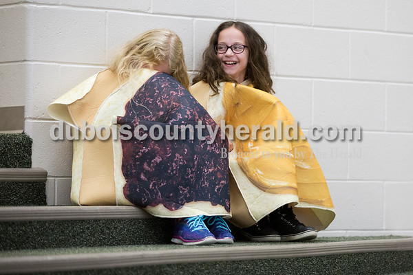 """Cedar Crest Intermediate School fifth-graders Sophia Gentry, left, and Anna Hulsman, dressed as peanut butter and jelly, laughed together after their part in their class' performance set to the song """"Eat It"""" by """"Weird Al"""" Yankovic at the 11th annual lip sync show at the school in Bretzville on Wednesday. Sarah Ann Jump/The Herald"""