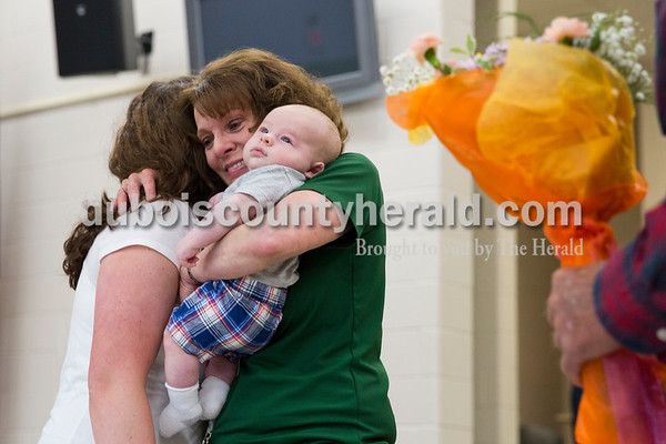 Cedar Crest Intermediate School sixth-grade teacher Janet Kamman  held her 2-month-old grandson Braxton Matthews as she hugged her daughter Keshia Matthews of Huntingburg and her husband Rick Kamman waited with flowers nearby after surprising her during the school's 11th annual lip sync show at the school in Bretzville on Wednesday. Kamman is retiring at the end of this school year. Sarah Ann Jump/The Herald