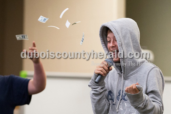 """Cedar Crest Intermediate School sixth-grader Jaron Wiseman pretended to rap as his classmate Logan Lehmkuhler threw fake dollar bills during their class' performance set to the song """"September"""" by Earth, Wind and Fire at the 11th annual lip sync show at the school in Bretzville on Wednesday. Sarah Ann Jump/The Herald"""