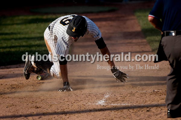 Tegan Johnston/The Herald Jasper's Evan Aders slid into home plate scoring a run during Thursday's Class 3A sectional championship at Ruxer Field in Jasper. Jasper defeated Vincennes Lincoln 8-4.