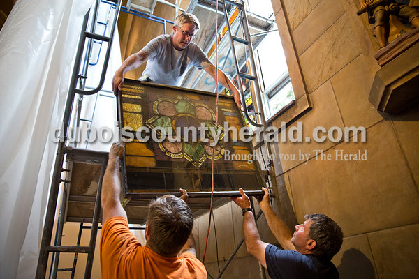 Sarah Ann Jump/The Herald Conrad Schmitt Studios employee Kevin Slager of New Berlin, Wis. passed a stained glass window panel down the scaffolding to his co-worker Brian Hummer of Waukesha, Wis., left, and church maintenance supervisor Pat Gehlhausen of Jasper at St. Joseph Catholic Church in Jasper on Tuesday morning.