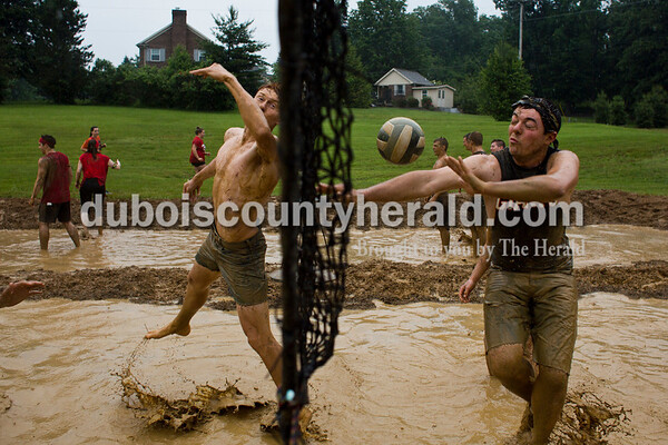Tegan Johnston/The Herald Jasper senior Luke Wagner, left, and Adam Krempp swung for the ball during Wednesday's mud volleyball tournament at Jasper High School. The senior class persisted through the rain in order to partake in their traditional mud volleyball tournament during their last week of school.