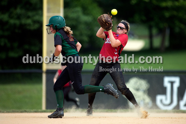 Vincennes Lincoln's Kaylee Lange ran past as the ball bounced out of the mitt of Southridge's Bre Wilkey during Saturday's 3A softball sectional championship game in Jasper. Vincennes Lincoln defeated Southridge 10-2. Sarah Ann Jump/The Herald